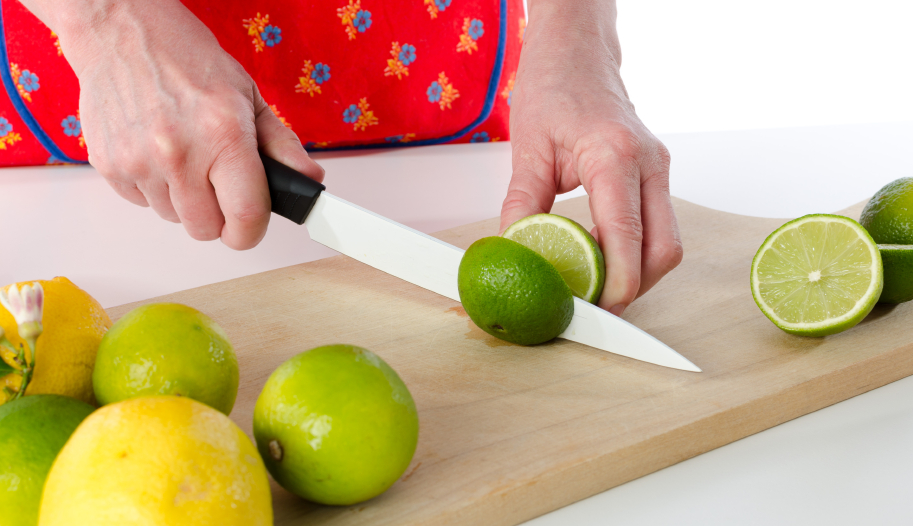 Woman cutting a lime in half on a cutting board